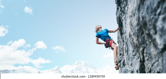 man rock climber with long hair. side view of young man rock climber in bright red shorts climbing the challenging route on the cliff on the blue sky background. rock climber climbs on a rocky wall.