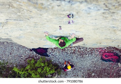 A man is a rock climber on a rock. Friends go in for sports in the open air. Girl in helmet insures partner.