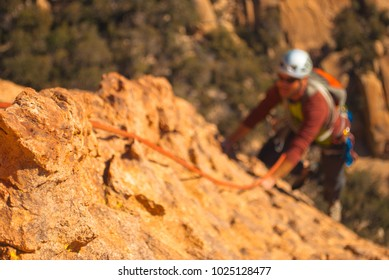 Man rock climbing in southern Arizona desert with shallow depth of field.