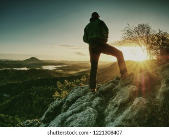 Man in rocks. Climbing hiking silhouette in fall mountains.  The climber in inspirational sunrise landscape on mountain peak.