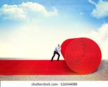 man roll huge red carpet