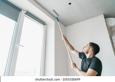 A man with a roller in his hands paints the ceiling in the gray color near the window of his house. Repair in the interior of the room repainting walls and ceiling.