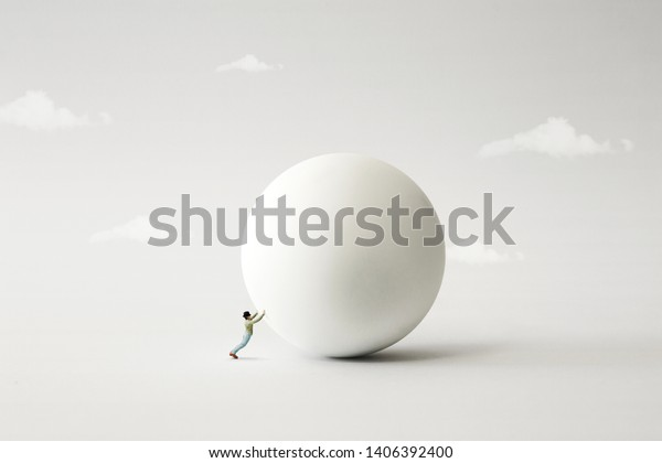 man rolling big heavy ball, surreal concept