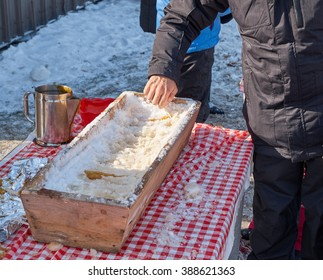 a man rolling hot maple syrup on snow