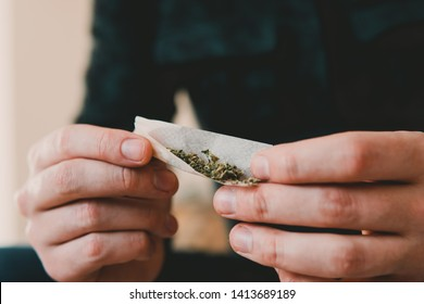 Man rolling a marijuana joint. Man preparing and rolling marijuana cannabis joint. Drug use. Close up . Close up of addict lighting up marijuana joint with lighter. Drugs narcotic concept.
