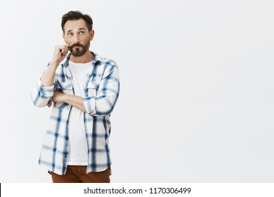 Man rolling moustache while looking up with serious and thoughtful expression, thinking, making choice or deciding something in mind, talking with conscience, standing over gray background