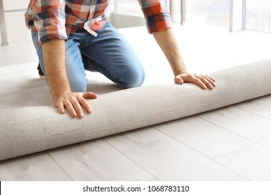 Man rolling out new carpet flooring in room