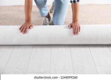 Man rolling out new carpet flooring indoors, closeup. Space for text