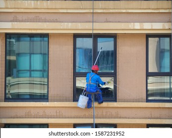 Man rope access cleaning glass windows outside building, He wearing safety helmet and carrying bucket with water, hose and mop.