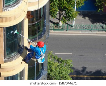 Man rope access cleaning glass windows outside building with mop. He wearing red safety helmet and carrying bucket with water inside and hose.
