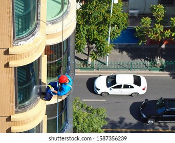 Man rope access cleaning glass windows outside building with hose and water, He wearing red safety helmet and carrying bucket with water and mop.