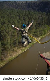 Man ropejumper jumps into the abyss with a safety rope from a great height above the river and the forest.