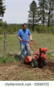 Man rototilling the ground, getting it ready for a garden.