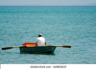 Man row a small wooden rowboat dinghy over calm water in the ocean.