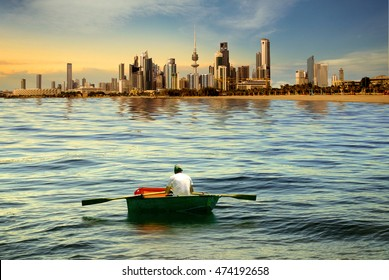 A man rowing boat on the sea of kuwait city during sunset
