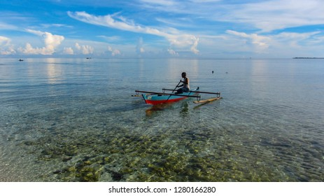 A man rowing his wooden boat to the clear blue sea, Saleman beach of Saleman Village, Manusela National Park, Seram island, Maluku, Indonesia, December 2013