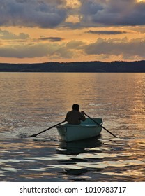 A man rowing at sunset. Ebeltoft harbour, Denmark.