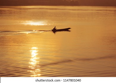 man rowing wooden boat in the  sunset silhouettes