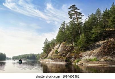 man rows on boat in beatiful nordic rocky bay. Big slanted pine on granite cliff.  Baltic sea, gulf of Finland