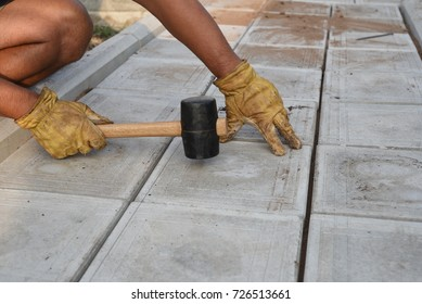 Man with a rubber mallet taps tiles on a pathway as part of a DIY construction project at home