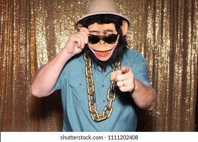 Man in a Rubber Monkey Mask while in a Photo Booth at a party or wedding.