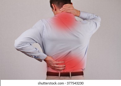 Man rubbing his painful back close up. Business man holding his lower back. Pain relief concept