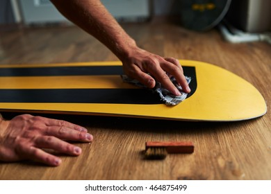 man rubs snowboard sponge wax on the wooden floor