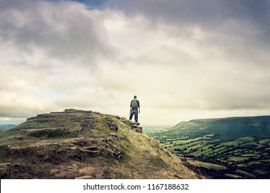 A man with rucksack looking out from the top of a hill with views of hills and fields. Black Hill, Brecon Beacons, UK