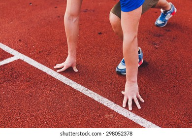 Man runner in blue shirt and shorts and sport shoes in steady position before run at start of race track preparing for run on a stadium unrecognizable no face focus on hands