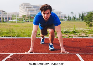 Man runner in blue shirt and shorts and sport shoes in steady position before run at start of race track preparing for run on a stadium with university campus on background