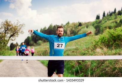 Man runner crossing finish line in a race competition in nature.
