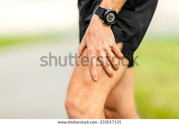 Man runner holding painful leg and muscle on running training outdoors in summer nature, sport jogging physical injury when working out, pain. Health and fitness concept with sore body