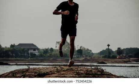 The man with runner on the lake be running for exercise.Run for health concept.