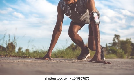 The man with runner on the street be running for exercise.Athlete running man - male runner listening to music on smartphone.Jogger training with smart phone armband.