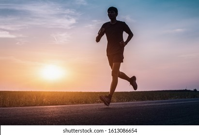 The man with runner on the street be running for exercise. - Image