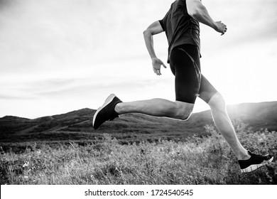 man runner run on mountain trail in rays of summer sunset