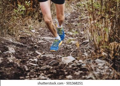 man runner skyrunners running marathon on track of dirt and stones