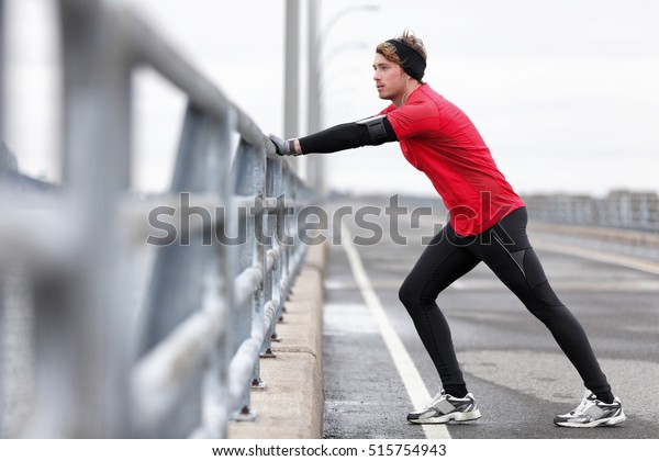 L'hiver, un coureur qui s'étire les jambes avant de faire de l'exercice court à l'extérieur dans la rue urbaine de la ville. Un athlète portant une montre à puce, un bracelet téléphonique pour l'application musicale et des gants chauds, un bandeau, de longs culottes en sous-vêtements.