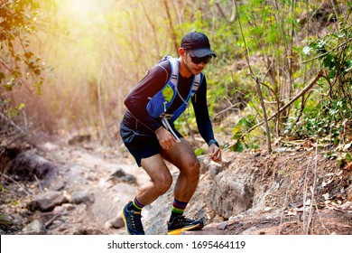 A man Runner of Trail and athlete's feet wearing sports shoes for trail running in the forest