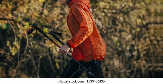 man runner with trekking poles in red jacket run in background of autumn trees with yellow leaves