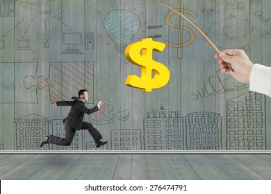 Man running after 3D golden dollar sign bait on fishing rod hand holding, with business concept doodles wood wall background