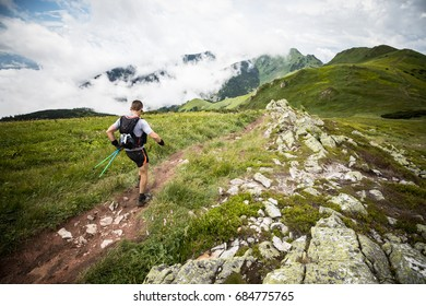 man running alone on the dirty muddy trail in the mountains after a summer rainy storm