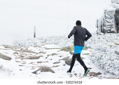 man running alone in winter on foggy high mountains trail