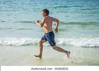 man is running along the beautiful beach, enjoying the water