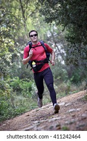 Man running along a forested trail