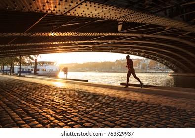 Man running along the Rhone river under a bridge on a sunny, autumn day. Lyon, France