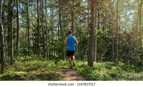 Man running along a trail in a forest, outdoor trailrunning