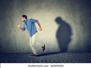 Man running away from his sad gloomy fat shadow on the wall. Mental health and body weight control concept