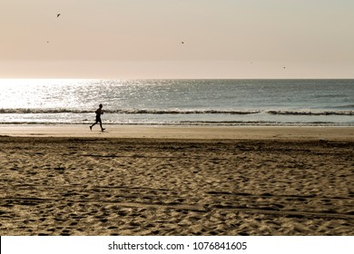 Man running for the beach in a sunny morning of summer.