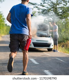 Man running with a car extinguisher to help another driver to extinguish car fire